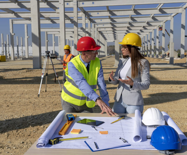 Man and Woman in Yellow Hardhats Disscus a Construction Project on Site. Business, Building and Teamwork Concept.